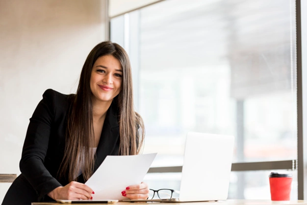 Latina office worker business attire on a stand-up desk with a laptop and holding papers