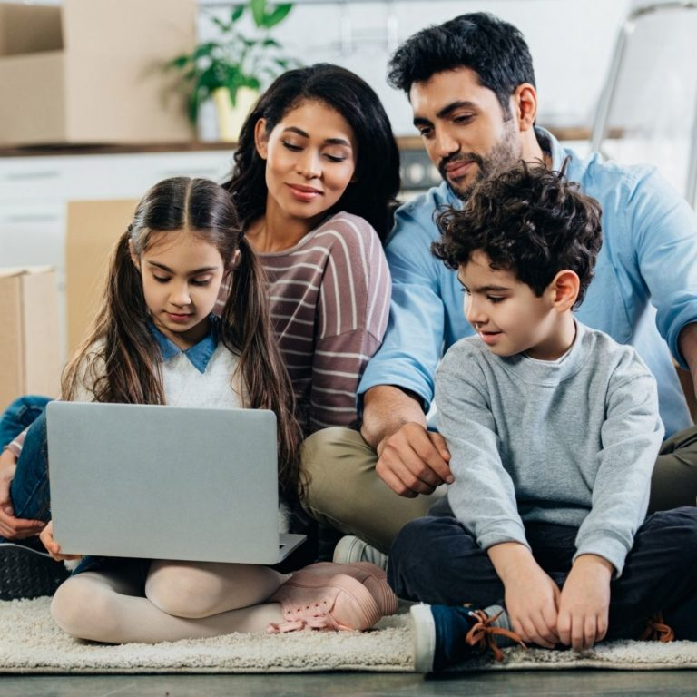 Latino family with mom, dad, and two children sitting around a laptop.